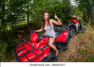Happy beautiful couple driving four-wheelers ATV. Girl is leading the way and giving the thumb up. Tilt shift lens blur effect