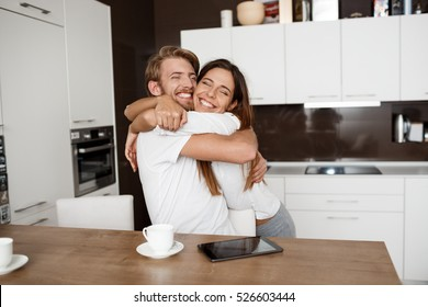 Happy beautiful couple embracing smiling at kitchen in morning.