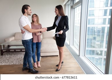 Happy beautiful couple and friendly realtor handshaking making real estate deal after signing sale purchase agreement or rental contract. Businesswoman and clients shaking hands, full length portrait