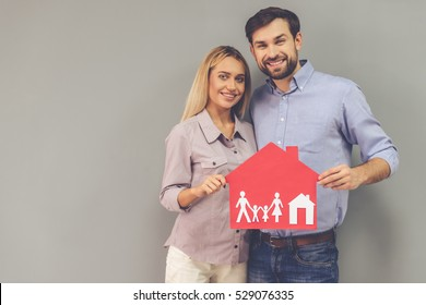 Happy beautiful couple is holding paper house, looking at camera and smiling, on gray background