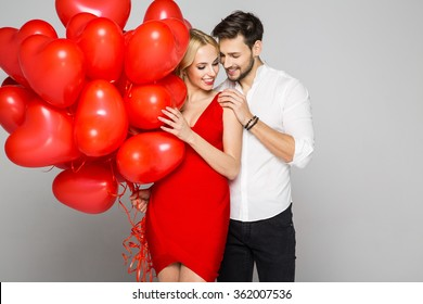 Happy beautiful couple looking at each other and holding balloons heart. Valentine's day.
