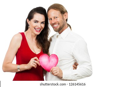 Happy beautiful couple smiling and holding a love heart. Isolated on white.