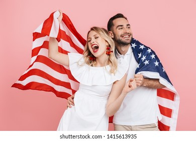 Happy beautiful couple standing isolated over pink background, carrying american flag, celebrating