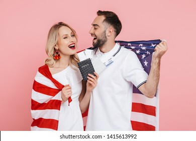 Happy beautiful couple standing isolated over pink background, carrying american flag, celebrating, showing passport