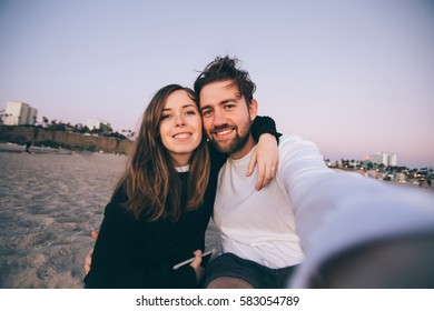 Happy beautiful couple taking selfie on the beach in California for travel blog. Concept of love and happiness.