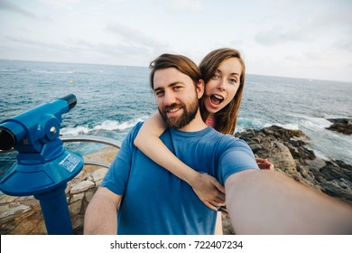 Happy beautiful couple taking selfie on the beach in Spain for travel blog. Concept of love and happiness.