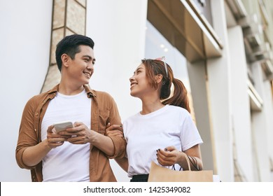 Happy beautiful couple using smart phone and shopping together.