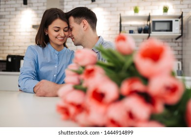 Happy beautiful cute young couple are sitting together on the kitchen with flowers. Love, celebration, romantic, st. Valentine's day, women day, birthday, date.