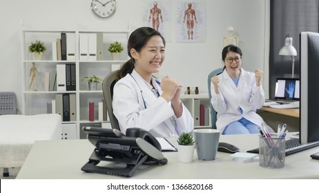 Happy beautiful dentists women smiling showing winning yes fist sign in dental clinic cabinet. cheerful doctors laughing staring at pc monitor sitting at working desk celebrate in healthcare office.
