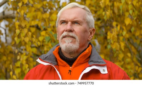 Happy beautiful elderly man with gray hair in orange sportswear on a background of autumn trees with yellow leaves