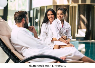 Happy beautiful family in bathrobes are joyful together while sitting in the spa salon