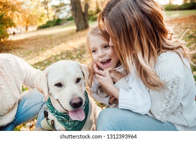 Happy beautiful family with dog labrador is having fun  are sitting on green grass in park.