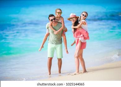 Happy beautiful family of four on white beach