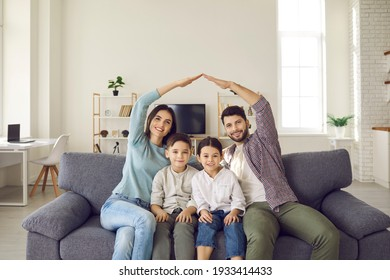 Happy beautiful family of four sitting on sofa at home. Smiling mom and dad doing arm roof gesture above little son and daughter. Mortgage, house insurance, children protection, future plans concept