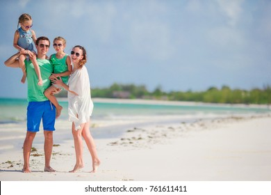 Happy beautiful family with kids together on tropical beach during summer vacation
