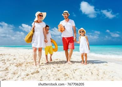 Schöne Familie mit Kindern, die während Sommerferien am tropischen Strand spazieren gehen