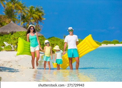 Happy beautiful family on white beach with inflatable air mattresses and toys