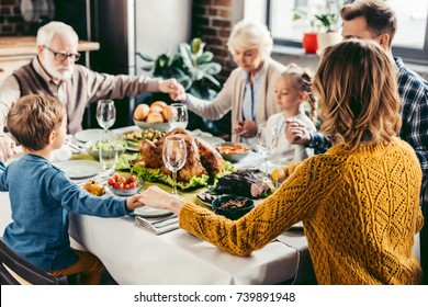 happy beautiful family praying before holiday dinner on thanksgiving