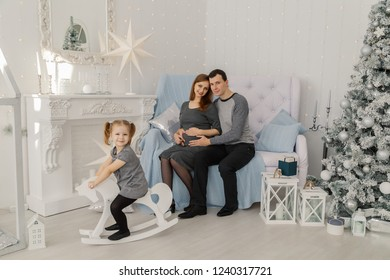 Happy and beautiful family of three at a festive bright New Year's room.
