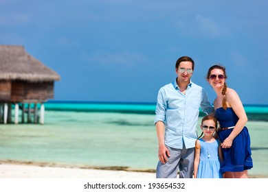 Happy beautiful family of three on a beach during summer vacation