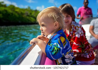Happy beautiful fashion family, children and parents, dressed in hawaiian shirts, enjoying day trip with speed boat in Mauritius