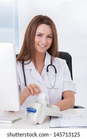 Happy Beautiful Female Doctor Inserting Credit Card Into Scanner