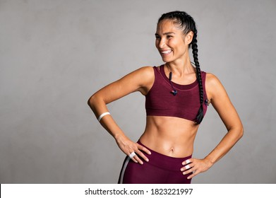 Happy beautiful fit woman laughing and looking away after gym exercise isolated on grey background. Middle aged woman wearing sports bra on gray wall with copy space. Carefree fitness girl resting.