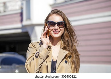 Happy beautiful girl calling by phone in spring street