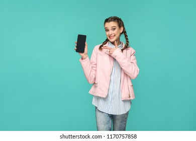 happy beautiful girl in casual or hipster style, pigtail hairstyle, standing, holding and pointing at mobile display, screen with toothy smile, Indoor studio shot, isolated on blue or green background