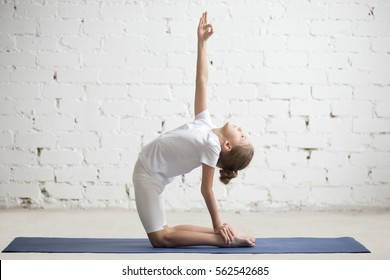 Happy beautiful girl child practicing yoga, stretching in Ustrasana exercise, Camel pose, working out, wearing sportswear, t-shirt, pants, indoor full length, white loft studio background