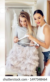 Happy and beautiful girl chooses a luxurious outfit.The stylist helps you choose the right one look. Girls choose dress. Luxury dress in stylish studio