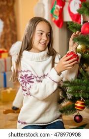 Happy beautiful girl decorating Christmas tree at living room