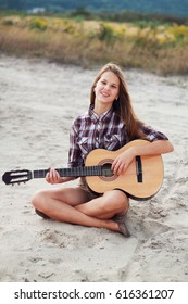 Happy beautiful girl in field with guitar