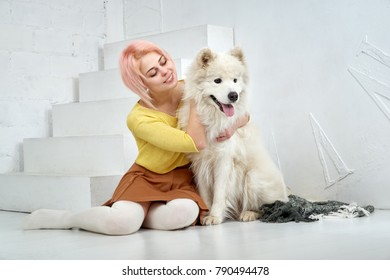 Happy beautiful girl and her big white dog sitting with pleasure in the arms. A beautiful young woman and her pet are best friends. Hug, play and enjoy life.