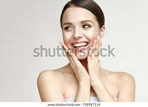 Happy beautiful girl holding her cheeks with a laugh   looking to the side. Pretty woman   clean fresh skin . Expressive facial expressions  .Cosmetology , beauty and Spa