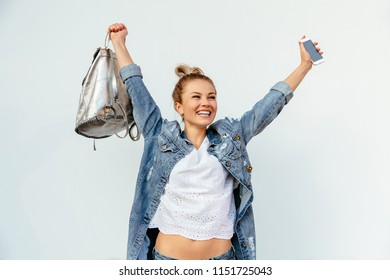 Happy beautiful girl holding a mobile phone and celebrating win, showing victory sign. Woman dressed in stylish denim jacket, with backpack. On white background.