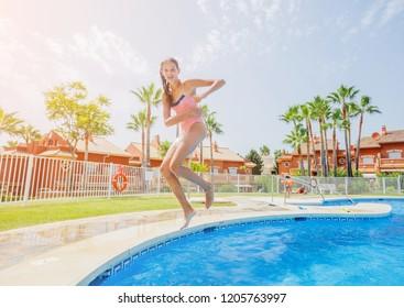 Happy beautiful girl jumping and having fun in the pool