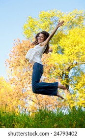 Happy beautiful girl jumping of joy on a fall day