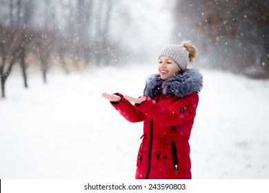 Happy beautiful girl in knitted hat and red winter coat, outdoors in park, rejoicing at snowfall, catching snowflakes with her palms