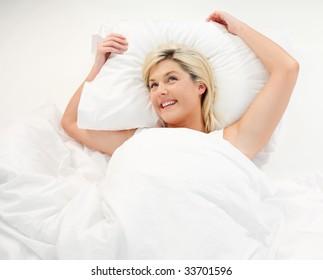 Happy beautiful girl lying in bed