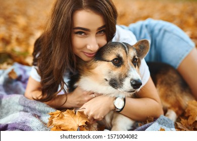 happy beautiful girl lying together with Welsh Corgi Pembroke dog in a park outdoors. Young female owner huging pet in park at fall on the orange foliage background. Concept friendship with dog and