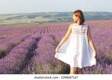Happy beautiful girl on a lavender background. Girl walking in meadow field. Family holiday in summer day.