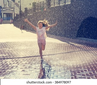 Happy beautiful girl running through the spray of water with the effect of toning