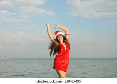 Happy and beautiful girl Santa Claus on the beach.