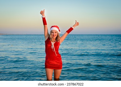 Happy and beautiful girl Santa Claus on the beach