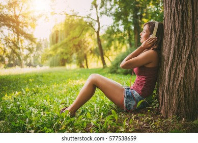 Happy beautiful girl sitting by a tree in a park and enjoying music.