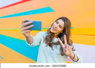 Happy beautiful girl with smart phone take selfie against urban grunge graffiti wall.