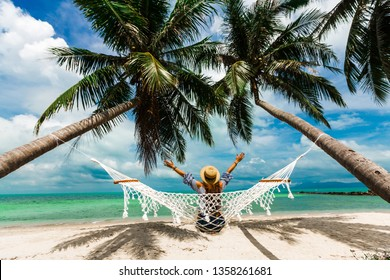Happy beautiful girl in a straw hat and shorts, sitting back on a beach hammock, arms raised to the top, between two palm trees, on the seashore of a tropical island, traveling summer vacation