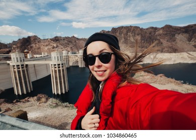 Happy beautiful girl tourist taking selfie photo near Hoover dam at Nevada Arizona boarder while travel in USA