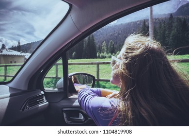 Happy beautiful girl traveling in a car across  at the mountains Dolomites, Italy. Europe